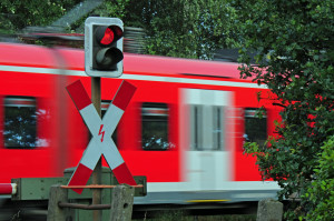 Ein Andreaskreuz mit rotem Blinklicht warnt Sie vor einem herannahenden Zug.
