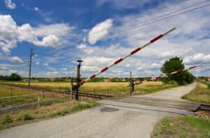 Ein beschrankter Bahnübergang wird durch ein Verkehrszeichen angekündigt.