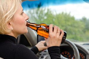 Bier trinken beim Autofahren: Keine gute Idee, aber legal.